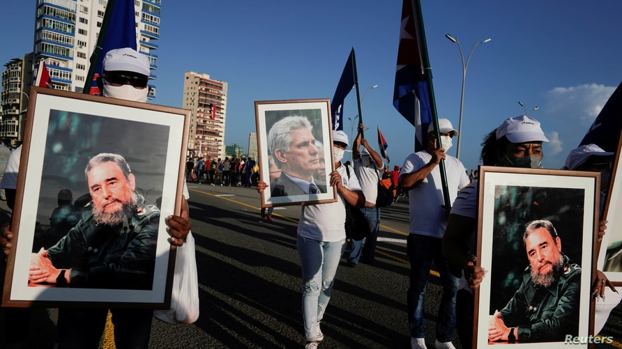 People carry images of Fidel Castro and Miguel Diaz-Canel during a rally in Havana