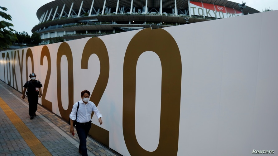 Pedestrians wearing protective masks, following the coronavirus disease (COVID-19) outbreak, walk in front of the National Stadium, the main stadium of Tokyo 2020 Olympics and Paralympics in Tokyo