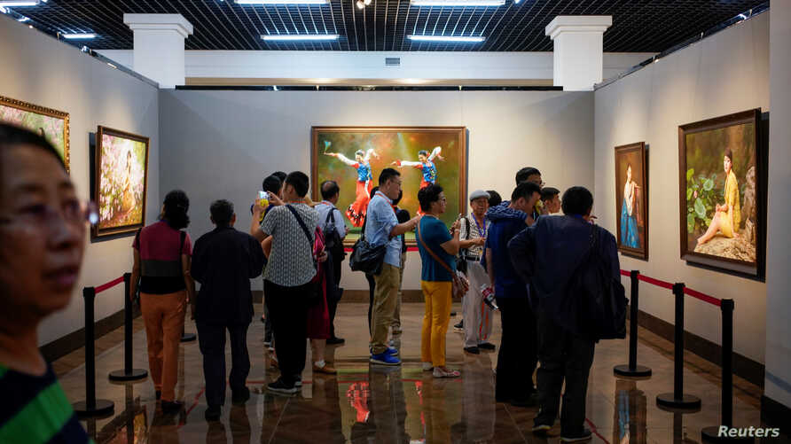 People look at paintings created by North Korean artists at the China-North Korea Cultural Centre in Dandong, Liaoning province…