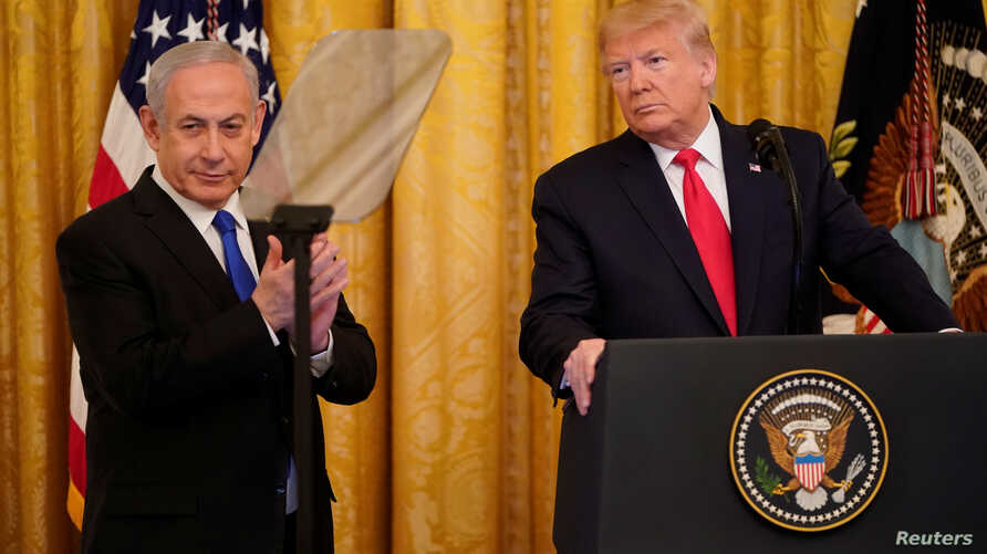 Israel's Prime Minister Benjamin Netanyahu applauds as he and U.S. President Donald Trump deliver joint remarks on a Middle…