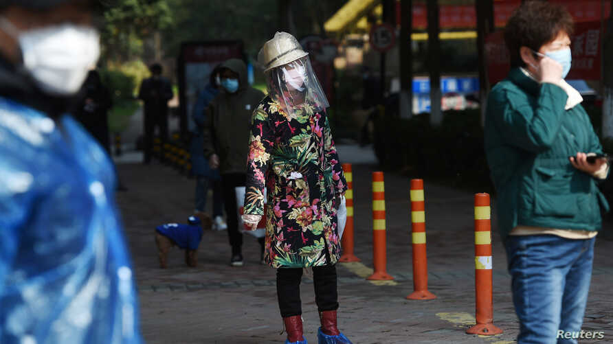 A resident wearing makeshift protective face shield stands in a line to collect food and necessities purchased through group…