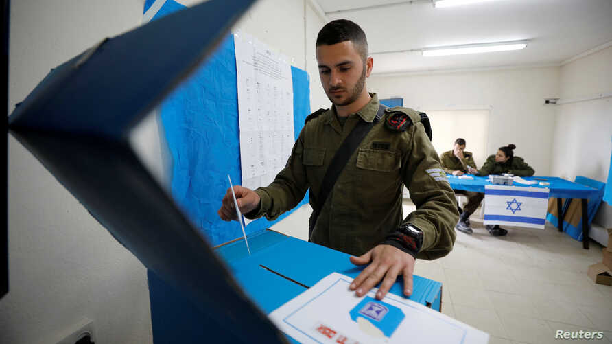 An Israeli soldier casts his ballot as he votes in Israel's national election in a mobile polling station at a military post…