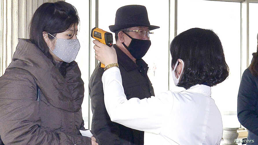 Volunteers carry out temperature screening during an anti-virus campaign in Pyongyang, North Korea in this image released by…