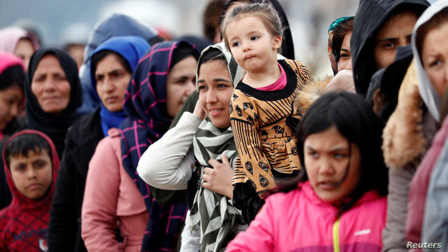 Migrants stand in line to receive food aid at Turkey's Pazarkule border crossing with Greece's Kastanies, near Edirne in Turkey…