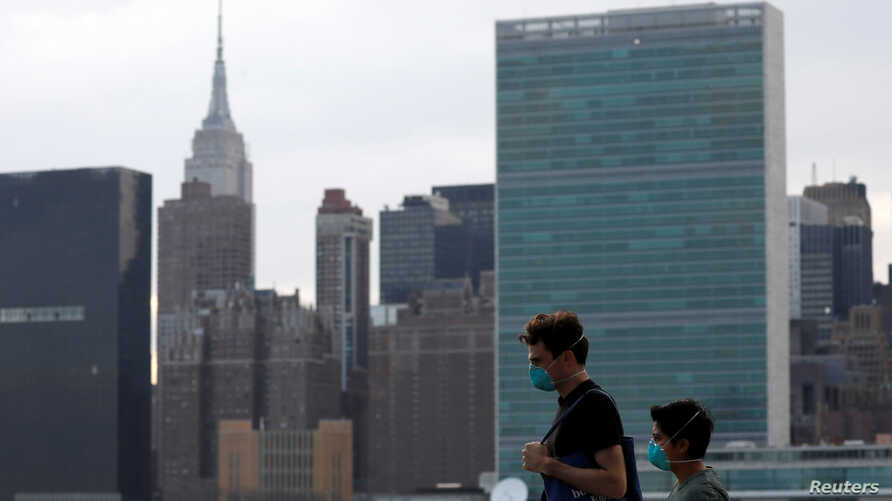 People in protective masks walk in front of the Manhattan skyline along the waterfront of Long Island City as the coronavirus…