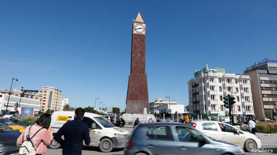 Cars and people pass by the clock tower at the end of Avenue Habib Bourguiba in Tunis, Tunisia March 12, 2020. Picture taken…
