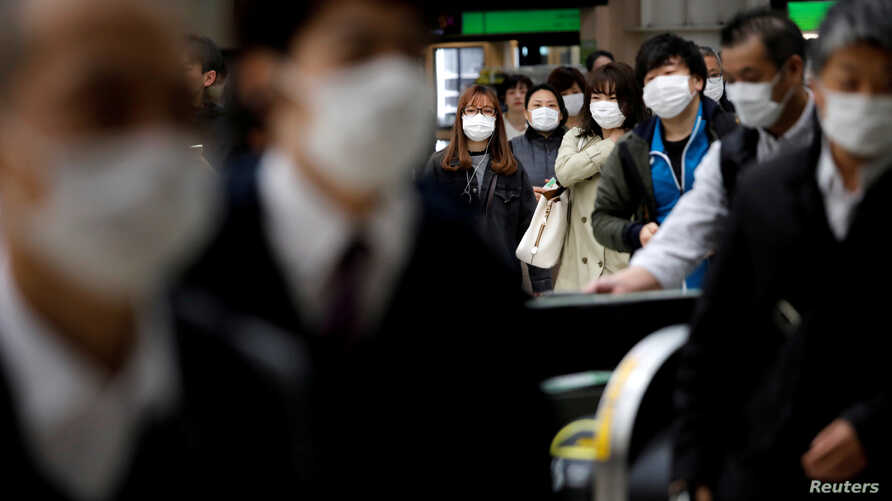 FILE PHOTO: Passengers wearing protective face masks, following an outbreak of the coronavirus disease (COVID-19), are seen at…