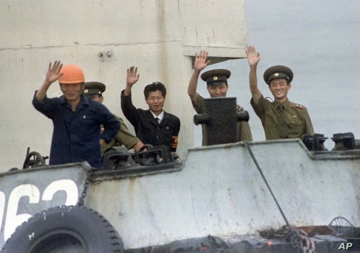 FILE - North Korean port officials wave from their launch as it approaches a South Korean ship near Yanghwa, North Korea, Aug. 19, 1997. Outsiders had been permitted to enter North Korea to attend a groundbreaking for construction of two light water nu...