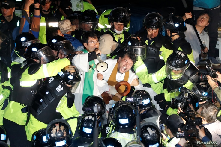 FILE - People scuffle with riot police during a protest opposing the deployment of a Terminal High Altitude Area Defense (THAAD) system in Seongju, South Korea, Sept. 7, 2017.