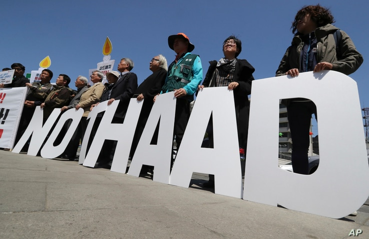"""FILE - Protesters hold letters reading """"NO THAAD"""" during a rally opposing the deployment of an advanced U.S. missile defense system called Terminal High-Altitude Area Defense, or THAAD, near the U.S. Embassy in Seoul, South Korea, April 26, 2017. The m..."""
