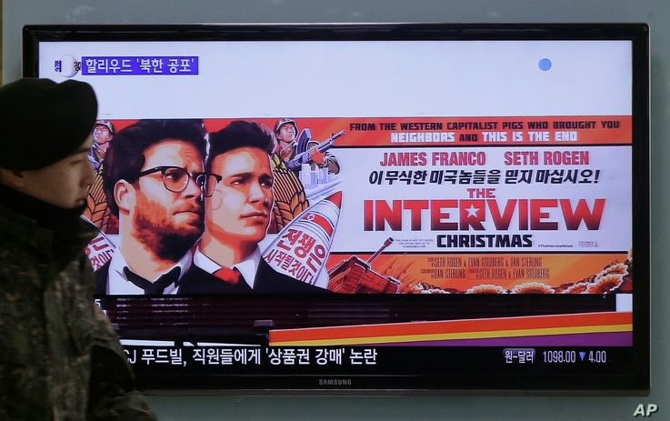 """FILE - A South Korean army soldier walks near a TV screen showing an advertisement of Sony Picture's """"The Interview,"""" at the Seoul Railway Station in Seoul, South Korea, Dec. 22, 2014."""