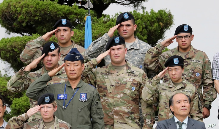 FILE - U.S. and South Korean soldiers salute during a change of command and responsibility ceremony at Yongsan Garrison, a U.S. military base, in Seoul, South Korea, Aug. 11, 2017.