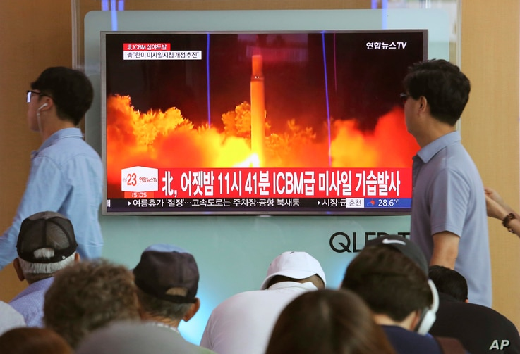 FILE - In this July 29, 2017 photo, People watch a TV news program showing an image of a North Korea's test launch of an intercontinental ballistic missile (ICBM), at the Seoul Railway Station in Seoul, South Korea.
