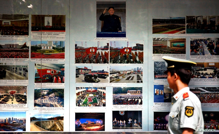 FILE - A paramilitary policeman looks at photos of North Korean leader Kim Jong Un and other North Korea-related images outside the North Korean Embassy in Beijing, Sept. 6, 2012. At the time, an official of a major Chinese investor said China should n...