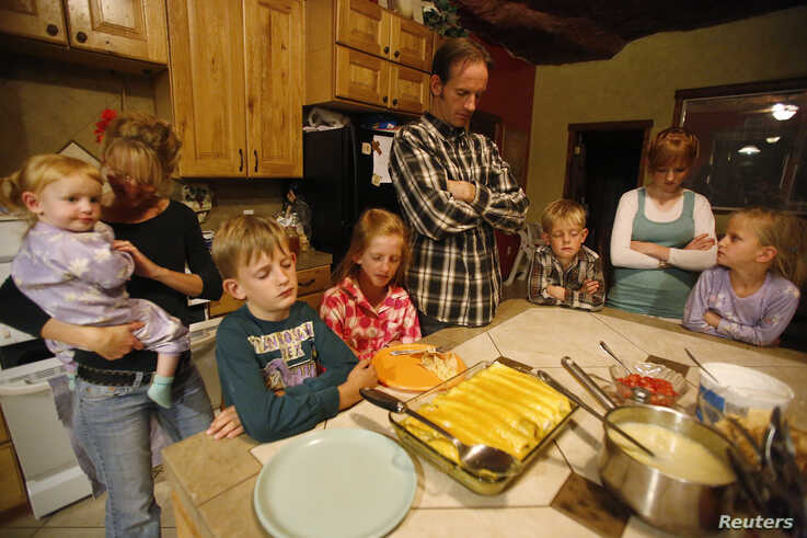 Enoch Foster, a fundamentalist Mormon practicing polygamy, prays before a meal with his first wife Catrina Foster, second from…