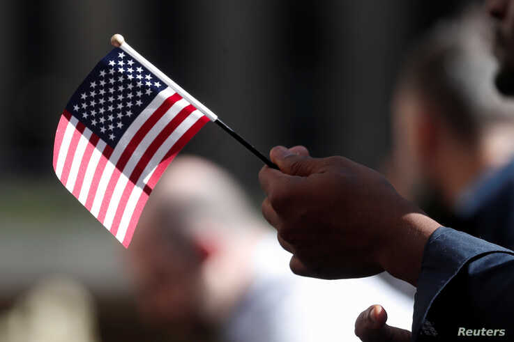 A citizenship candidate holds a flag during the U.S. Citizenship and Immigration Services (USCIS) naturalization ceremony at…