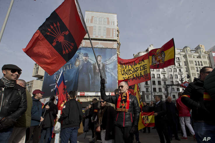 A man waves a Falangist flag ahead of a far-right march in Madrid, Spain, Sunday, Nov. 24, 2019. Hundreds of people nostalgic…