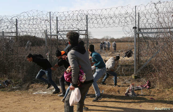 Migrants throw stones at a Greek military vehicle on the Turkish-Greek border at Turkey's Pazarkule border crossing with Greece…