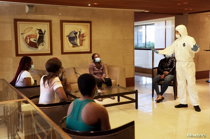 A health worker explains safety tips on the coronavirus disease (COVID-19) to migrant domestic workers from Africa before they…