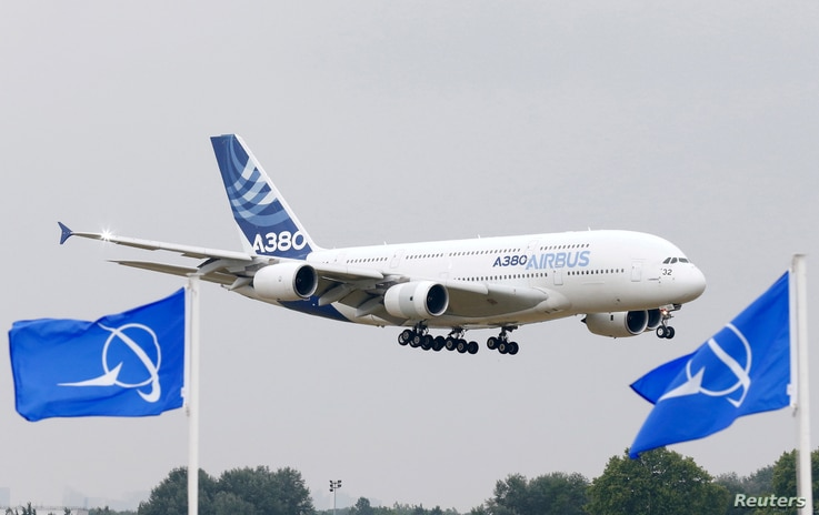 FILE PHOTO: An Airbus A380, the world's largest jetliner, flies over Boeing flags as it lands after a flying display during the…