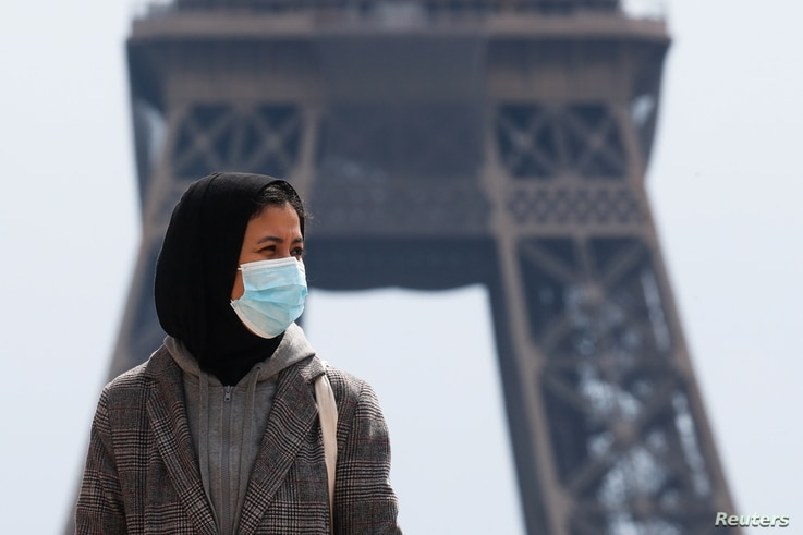 A woman, wearing a hijab and a protective face mask, walks at Trocadero square near the Eiffel Tower in Paris, France, May 2,…