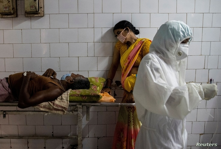 FILE PHOTO: A woman leans against a stretcher holding her husband in the corridor of the emergency ward of Jawahar Lal Nehru…