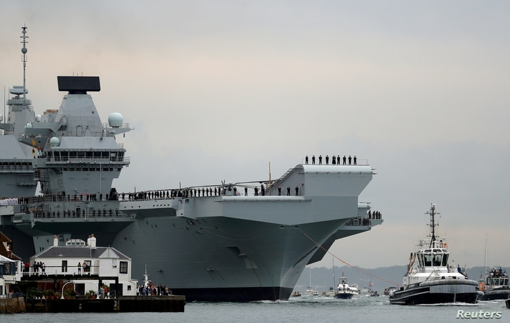 FILE PHOTO: Royal Navy aircraft carrier, HMS Queen Elizabeth, is towed by tugs as it arrives at Portsmouth Naval base, Britain…