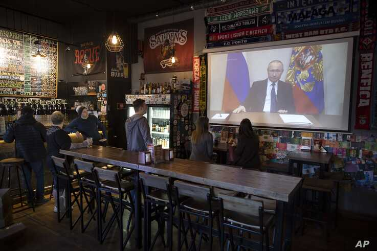 A few visitors and staff of the pub watching the broadcast of Russian President Vladimir Putin addresses Russian citizens on…