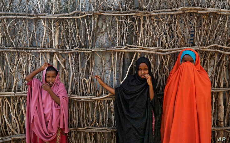 FILE - In this Tuesday, Dec. 19, 2017 file photo, Somali refugee girls stand by the fence surrounding their hut at Dadaab…