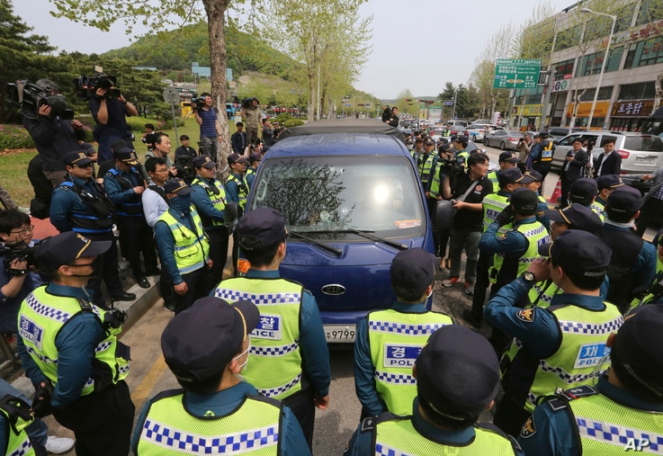 Police officers surround a vehicle containing anti-North Korea propaganda balloons during a rally to send them to North Korea,…