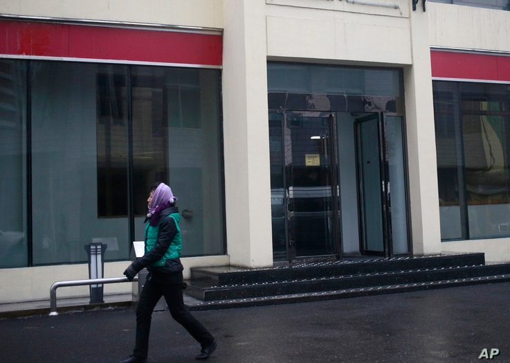 """In this  Dec. 21, 2018, photo, a North Korean woman walks past the entrance of Bugsae Shop, also known as the """"Singapore Shop,""""…"""