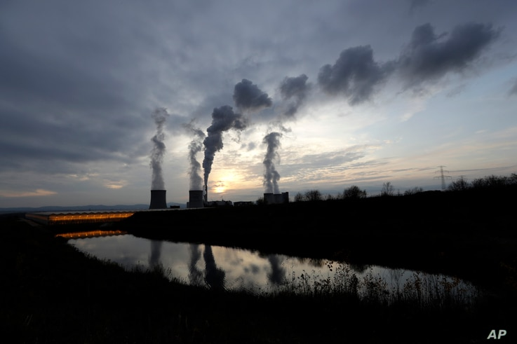 Smoke rises from chimneys of the Turow power plant located by the Turow lignite coal mine near the town of Bogatynia, Poland,…