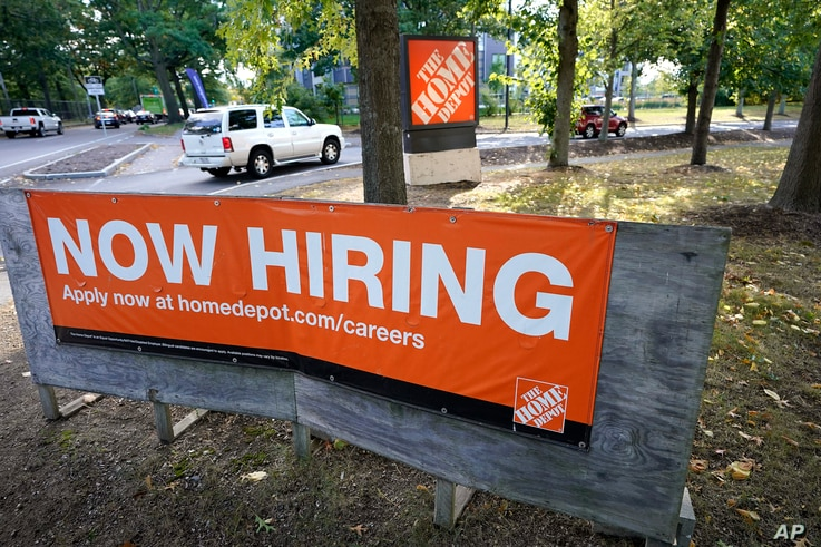 Vehicles drive past a now hiring sign as they enter a parking lot for a Home Depot store location, Wednesday, Sept. 30, 2020,…