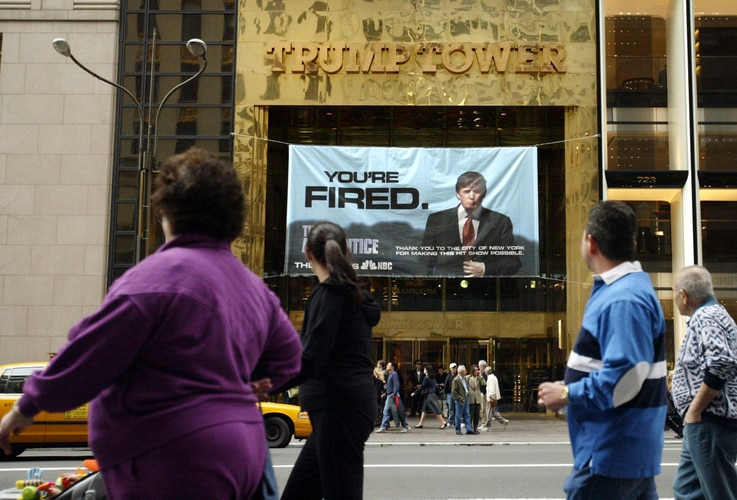 "FILE - In this March 27, 2004 file photo, passersby look at a sign from Donald Trump's television show, ""The Apprentice,"" hung…"
