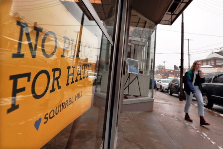"""A woman passes by a """"No Place For Hate"""" sign in a shop in Pittsburgh's Squirrel Hill neighborhood Monday, Feb. 11, 2019. Robert…"""