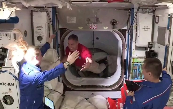 In this frame grab from NASA TV, astronaut Mike Hopkins, center, is greeted by astronaut Kate Rubins, left, as he enters the…