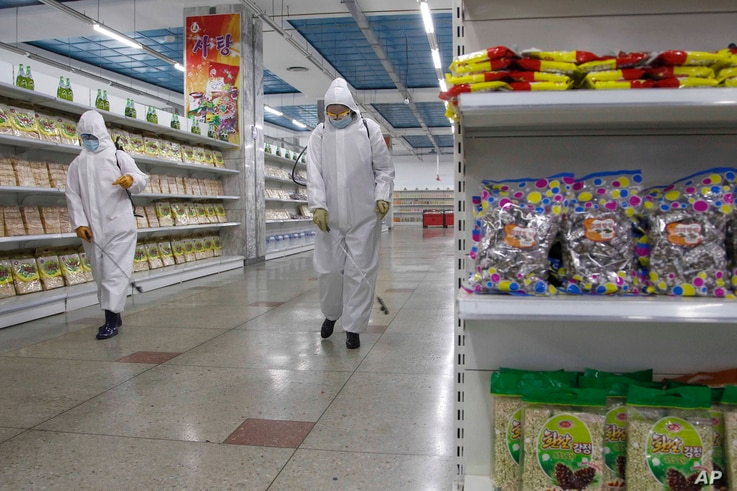 Staff of the Pyongyang Department Store No. 1 disinfect the store before it opens in Pyongyang, North Korea Monday, Dec. 28,…