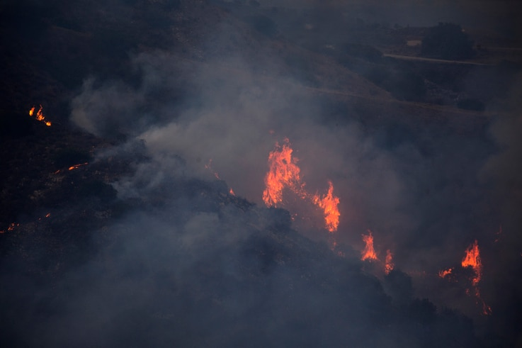 A wildfire burns a hillside in Fallbrook, northern San Diego County, Calif., Thursday, Dec. 24, 2020. (AP Photo/Ringo H.W. Chiu)