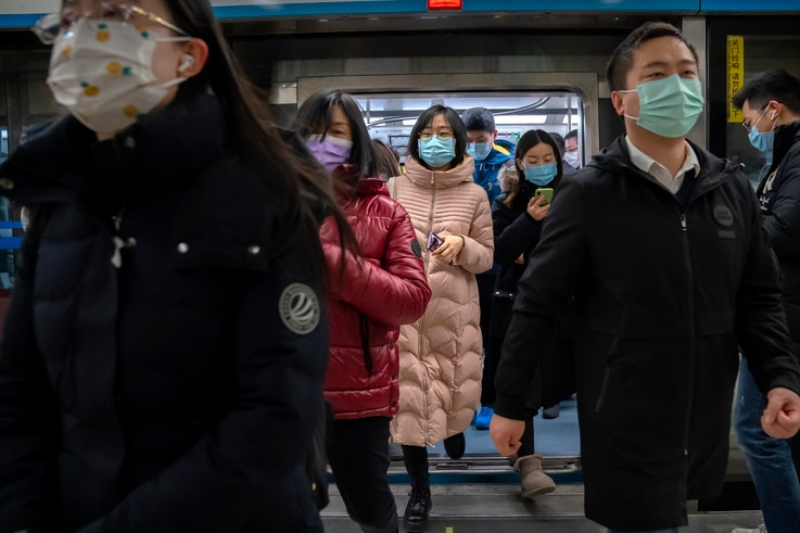People wearing face masks to protect against the spread of the coronavirus exit a subway train in Beijing, Wednesday, Jan. 27,…