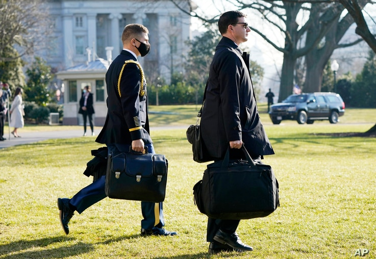 """A U.S. military aide, left, carries the """"President's emergency satchel,"""" also know as """"the football,"""" with the nuclear launch…"""