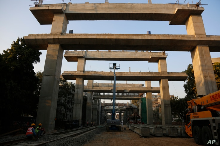 Indian laborers work at a Metro Rail project site in Ahmedabad, India, Monday, Feb. 1, 2021. India's government on Monday…