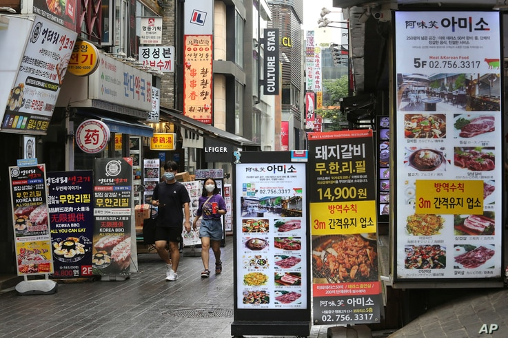 People wearing face masks to help protect against the spread of the coronavirus pass by banners showing the menu items of…