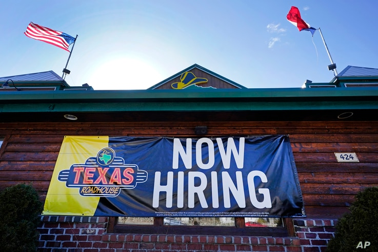 """A restaurant displays a """"Now Hiring"""" sign, Thursday, March 4, 2021, in Methuen, Mass.  The American job market delivered a…"""