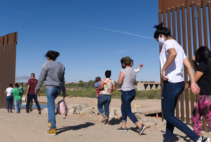 In this Tuesday, June 8, 2021, photo, a group of Brazilian migrants make their way around a gap in the U.S.-Mexico border in…