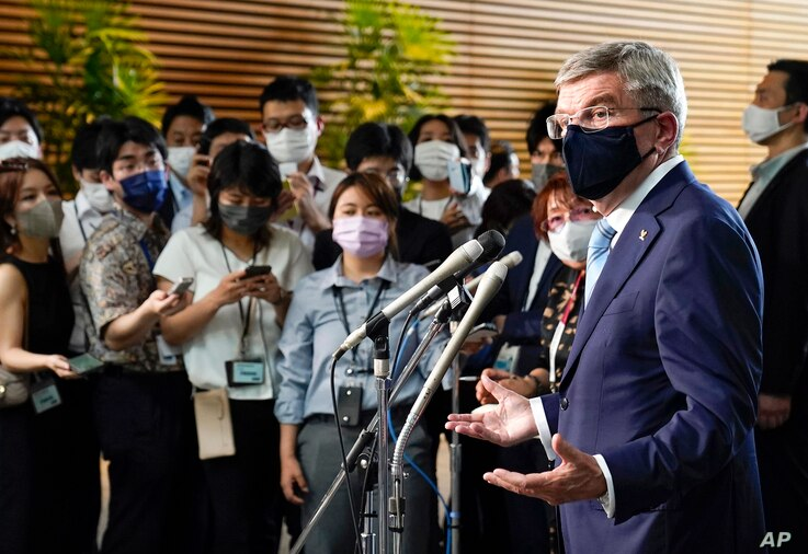 International Olympic Committee President Thomas Bach, right, speaks to journalists after meeting Japanese Prime Minister…
