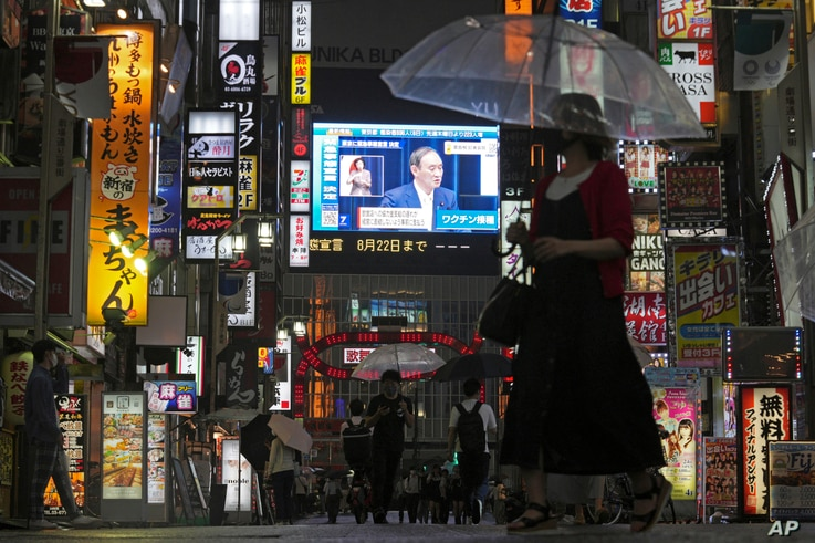 Pedestrians walk past a giant public TV with a live broadcast of a news conference by Japanese Prime Minister Yoshihide Suga…