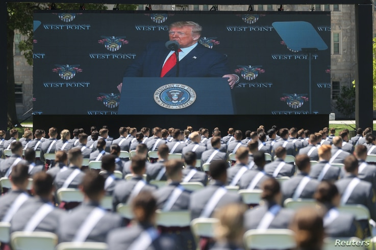U.S. President Trump is displayed on a screen as he delivers remarks to West Point graduating cadets during their 2020 United States Military Academy graduation ceremony at West Point, New York