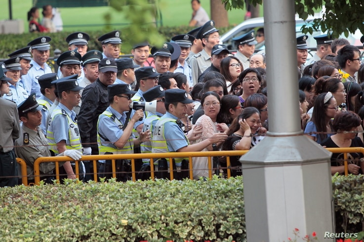 FILE PHOTO: Police officers remove fans standing outside the opening ceremony of the 17th Shanghai International Film Festival