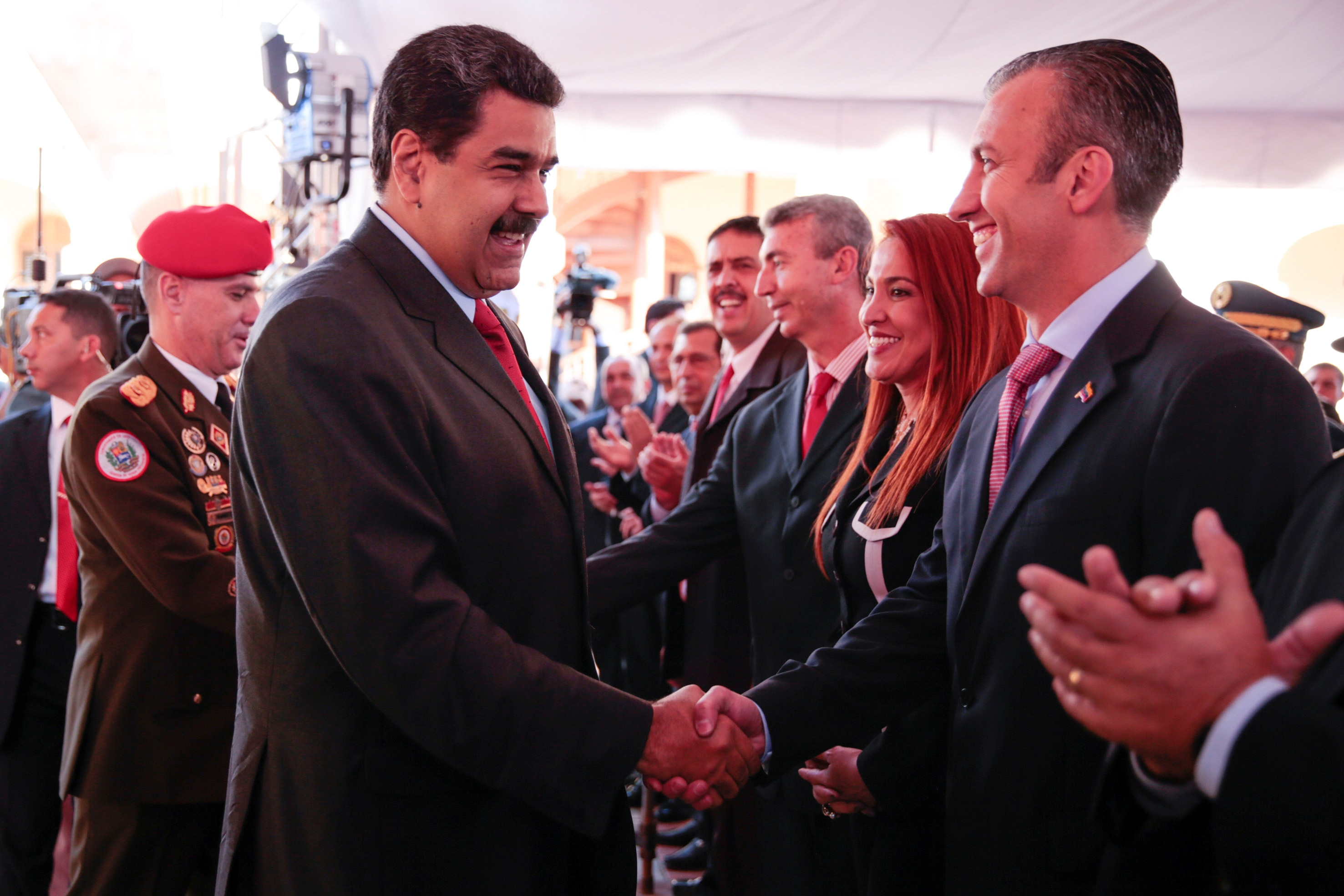 Venezuela's President Nicolas Maduro (C) shakes hands with Venezuela's new Vice-President Tarek El Aissami (R) during a meeting…