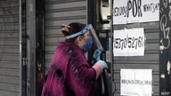 A woman wearing a face mask, shield and gloves takes away her order at a partially closed store during the lockdown imposed by…